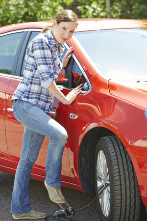 woman foot: Woman Inflating Car Tyre With Foot Pump