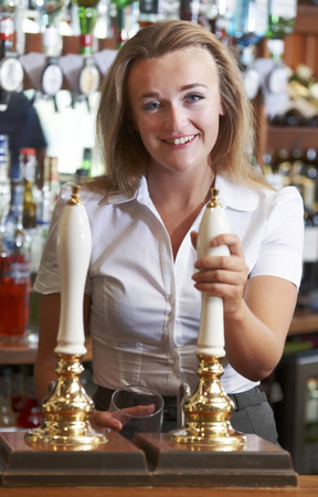 Female Bartender Serving Drink To Customer