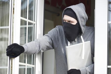 Cambrioleur rupture dans la maison et de voler ordinateur portable Banque d'images