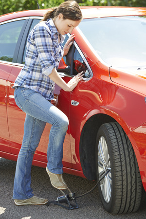 pumping: Woman Inflating Car Tyre With Foot Pump