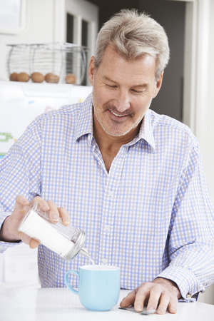 adding sugar: Mature Man Adding Sugar To Cup Of Coffee Stock Photo