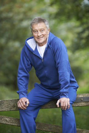 whilst: Senior Man Resting Whilst Exercising In Countryside Stock Photo