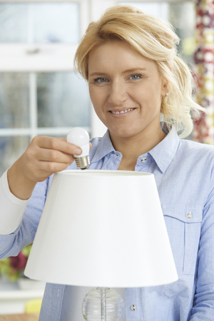 energy use: Woman Putting Low Energy LED Lightbulb Into Lamp At Home