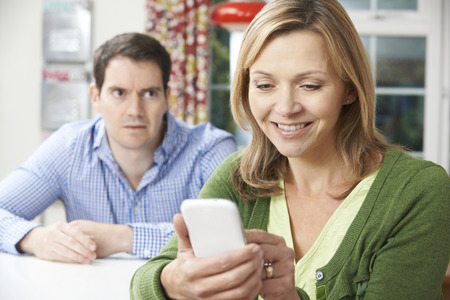 arguement: Unhappy Man Sitting At Table As Partner Texts On Mobile Phone