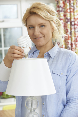 low energy: Woman Putting Low Energy Lightbulb Into Lamp At Home