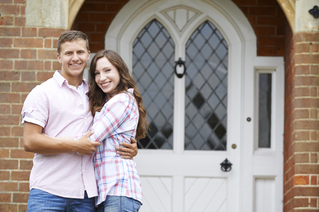 front house: Portrait Of Loving Couple Standing Outside Home