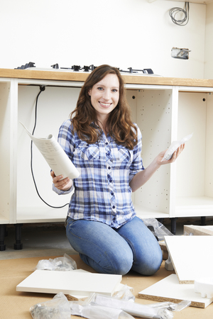 fitted: Woman With Self Assembly Furniture In Kitchen Stock Photo