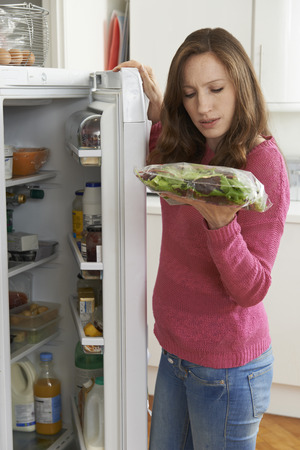 vertical fridge: Woman Checking Sell By Date On Salad Bag In Refrigerator Stock Photo