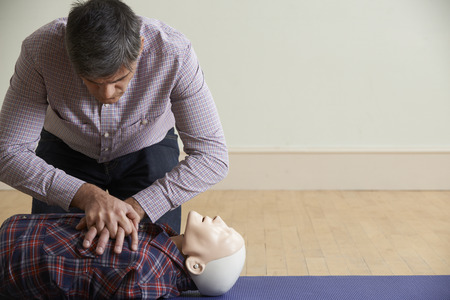 cpr: Man Using CPR Technique On Dummy In First Aid Class Stock Photo