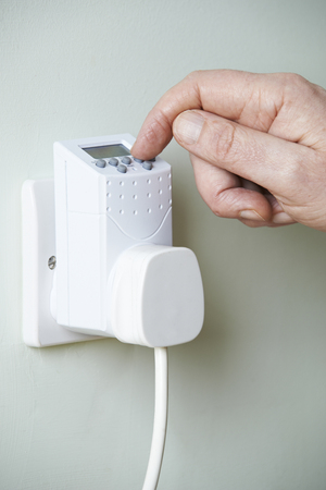 outlet: Close Up Of Hand Adjusting Timer Switch In Plug Socket