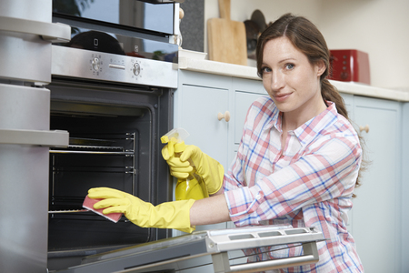 scrubbing up: Portrait Of Woman Cleaning Oven At Home Stock Photo