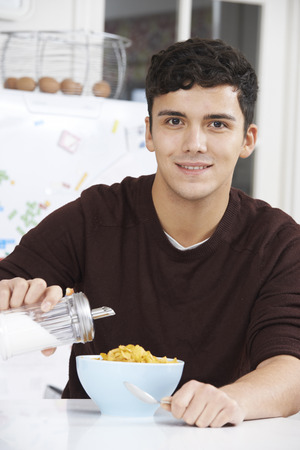 too much: Young Man Adding Sugar To Breakfast Cereal Stock Photo