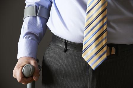 sick leave: Close Up Of Businessman Using Crutch