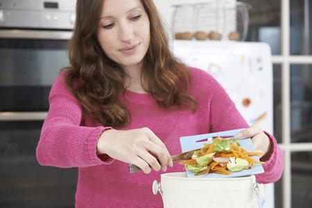 scraping: Woman Scraping Vegetable Peelings Into Recycling Bin