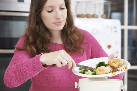 Une femme racler Leftovers aliments en Poubelle Banque d'images