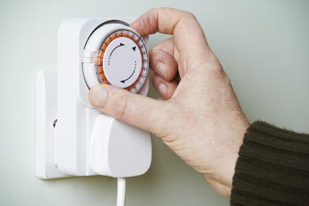 Man Adjusting Timer On Electrical Socket
