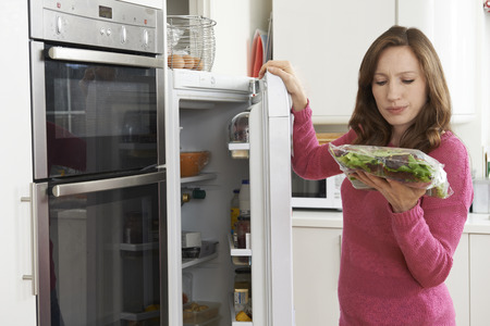 Woman Checking Sell By Date On Salad Bag In Refrigerator Stock fotó