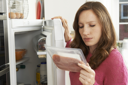Concerned Woman Looking At Pre Packaged Meat 스톡 콘텐츠