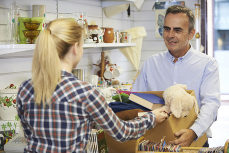 Man Donating Unwanted Items To Charity Shop