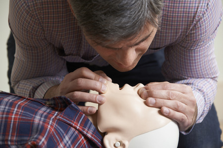 of the mouth: Man In First Aid Class Performing Mouth To Mouth Resuscitation On Dummy