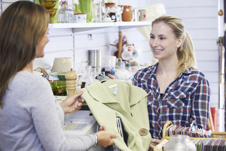 thrift store: Customer Buying Clothing In Charity Shop