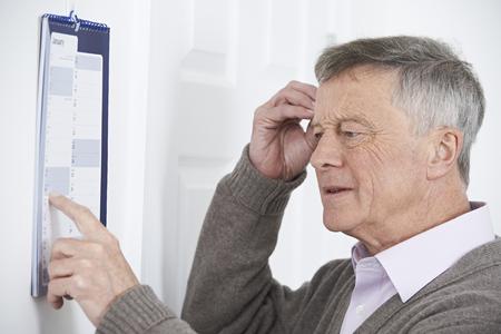 Confused Senior Man With Dementia Looking At Wall Calendar Archivio Fotografico