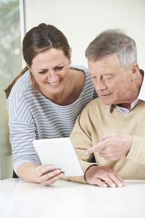 senior adult man: Senior Man And Adult Daughter Looking At Digital Tablet Together