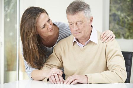 Confundido hombre mayor con la hija adulta en el hogar Foto de archivo