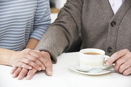 Close Up Of Woman Sharing Cup Of Tea With Elderly Parent Archivio Fotografico