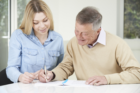 sudoku: Senior Man Playing Completing Sudoku Number Puzzle With Teenage Daughter