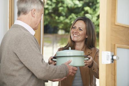 노인 이웃을 위해 식사를 잡는 여자