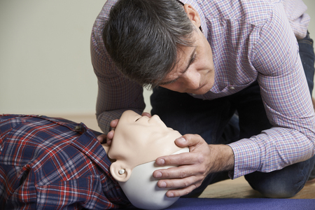 primeros auxilios: Hombre En la primera clase de Ayuda Comprobación de las vías respiratorias como la RCP Maniquí