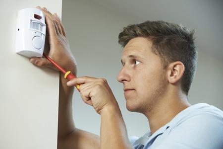 burglar: Security Consultant Fitting Burglar Alarm Sensor In Room