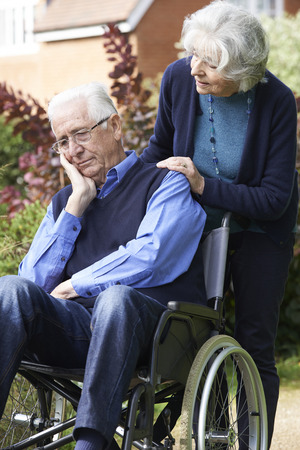 80s adult: Depressed Senior Man In Wheelchair Being Pushed By Wife Stock Photo