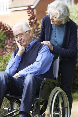 paraplegic: Deprimido hombre mayor en silla de ruedas que es empujado por la esposa