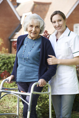 80s adult: Carer Helping Senior Woman To Walk In Garden Using Walking Frame