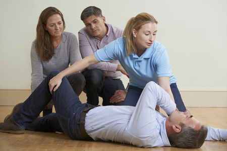 first class: Woman Demonstrating Recovery Position In First Aid Training Class