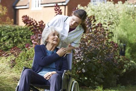 Carer Pushing Senior Woman In Wheelchair