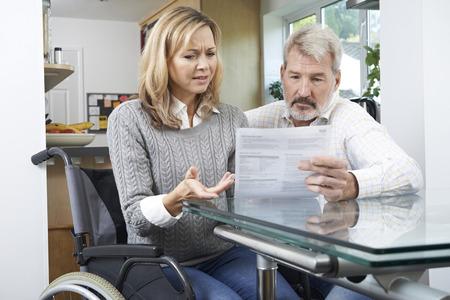 personas discapacitadas: Pareja frustrado con la mujer en silla de ruedas de leer la carta Foto de archivo