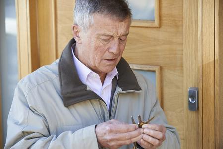 confundido: Confundido hombre mayor Un intento encontrar llave de la puerta