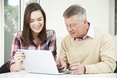 retirement community: Teenage Granddaughter Showing Grandfather How To Use Laptop Computer