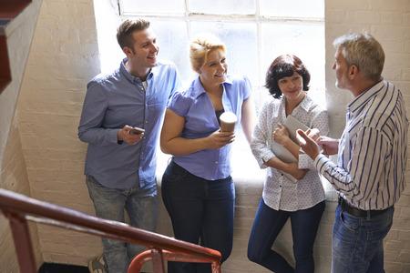 informal: Businesspeople Having Informal Meeting On Office Stairs Stock Photo