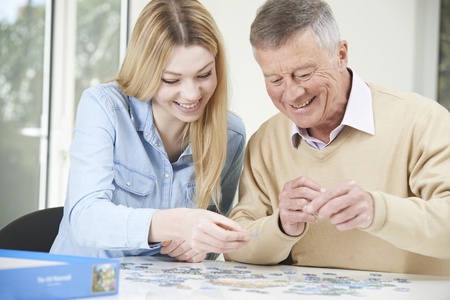 home care: Teenage Granddaughter Helping Grandfather With Jigsaw Puzzle