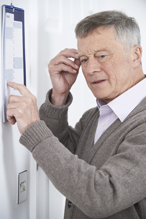 Confused Senior Man With Dementia Looking At Wall Calendar Stock fotó