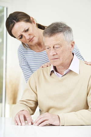 senior adult man: Confused Senior Man With Adult Daughter At Home Stock Photo