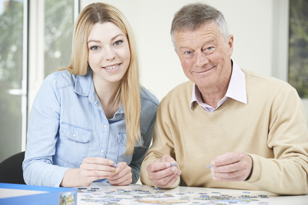 granddaughter: Teenage Granddaughter Helping Grandfather With Jigsaw Puzzle