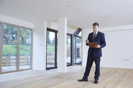 Mirando agente de bienes de pisos en vacante para la valoración Foto de archivo