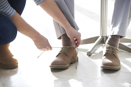 Adult Daughter Helping Senior Tie Shoelaces Stock Photo