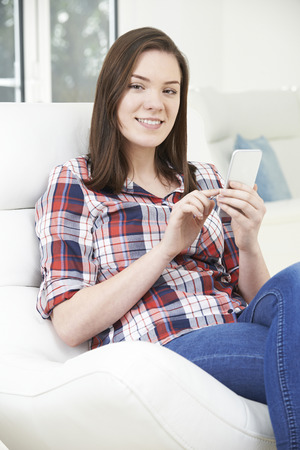 message sending: Teenage Girl Sending Text Message From Mobile Phone At Home Stock Photo