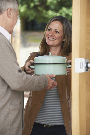 neighbour: Woman Bringing Meal For Elderly Neighbour Stock Photo